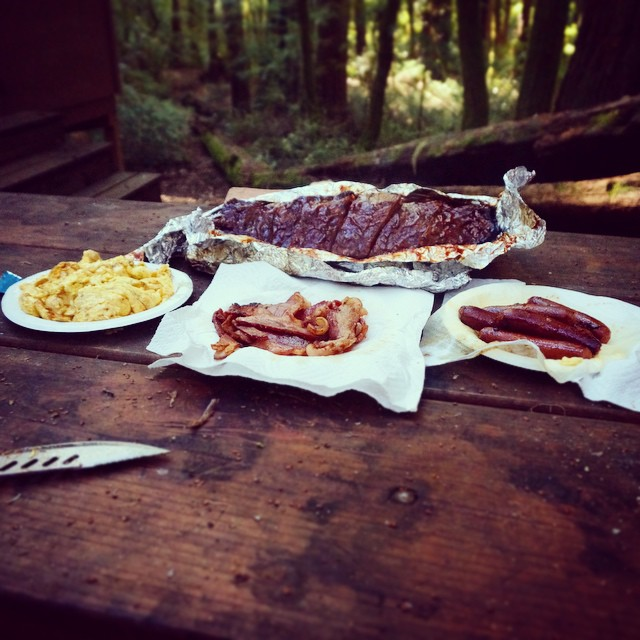 Big campin' breakfast! Rack of ribs, scrambled eggs, smoked bacon & sausages. All cooked over a live fire.