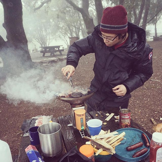 Grill duty. Trying out new #camping #gear from @biolitestove. Despite the rain, was able to cook off some bacon and sausages using chippings from a single log.  @mr.e.katt with the action shot.